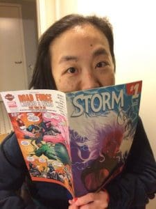 A picture of Alice Wong reading an issue of Storm comics