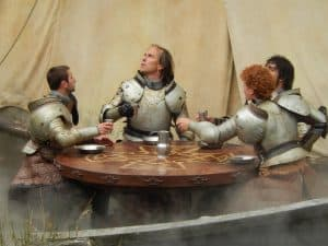 Four knights in armor (without their helmets) sit around a table with metal plates set before them. They are all white men, differentiated primarily by the color of their hair.